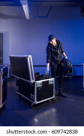 Roadie unpacking some high voltage power cables out of a flightcase, in preparation for a music concert at an event venue