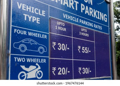 A roadside board showing parking fare for vehicles in North India.