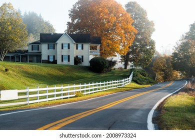 Roadside farmhouse house in countryside rural road highway in West Virginia, USA by mountain forest with colorful autumn fall trees foliage at sunrise morning