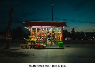 Blumenladen am Straßenrand während der Nacht. Der einsame Blumenladen spätnachts, mit Blumen sichtbaren Blumen unter Neonlicht.
