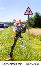 Roadside memorial next to a dangerous bend sign in France