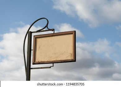 A roadside sign with blank space in against a blue sky with clouds.