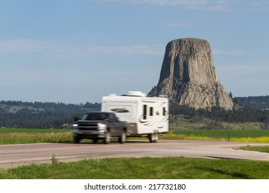 Roadside view of Devils Tower National Monument with a slow shutter sped to blur the moving vehicle in the foreground