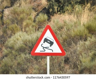 Roadsign indicating caution for slippery road, with symbol of a skidding car