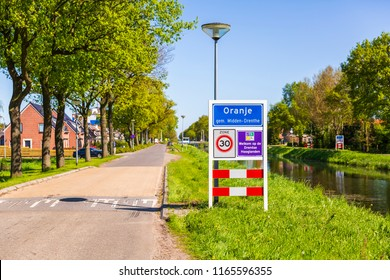Roadsign to welcome visitors and tourism to the small village Oranje, Drenthe, the Netherlands. Warm sunny day with clear bue sky.