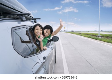 Roadtrip concept: Portrait of two happy children waving hands on the camera while sticking their head out the car window