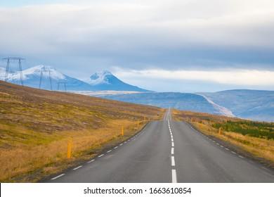 Reise durch Island, leere gepflasterte Straße, die über Berge führt, mit schneebedeckten Spitzen neben Stromleitungen