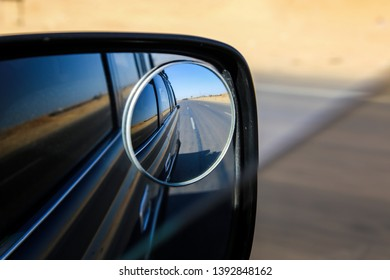 Roadtrip picture of side mirror; drive through dry desert area; warm summer drive