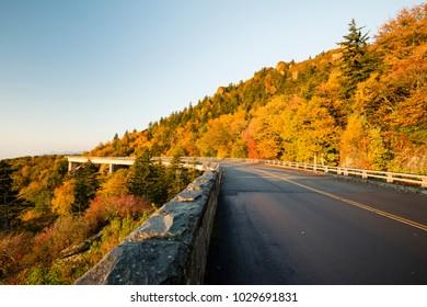 Roadway bridge skyline via duct around mountain in fall