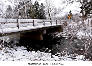 The roadway bridge is snow covered over the open water of the Pike River in a Wisconsin park early in the winter season.