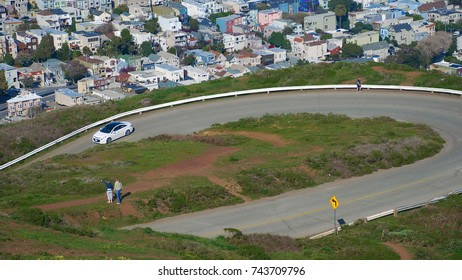 A roadway weaves through hills at Twin Peaks in San Francisco, CA as couple women overlook the city
