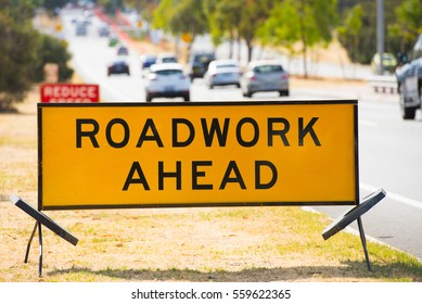 Roadwork ahead alarm sign at roadside, with traffic in blurred background.