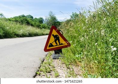 Roadwork sign by roadside in a lush greenery in summer season