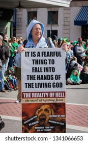 Roanoke, VA/USA - March 16, 2019 Woman holding religious sign in the street before the St Patrick's Day parade.