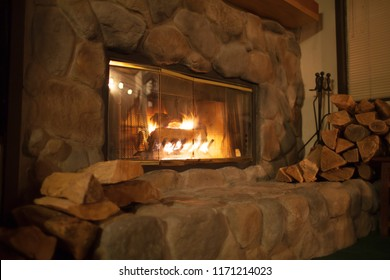Roaring fire in an arched stone fireplace