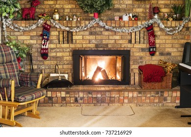 Roaring fire in a vintage brick fireplace decorated for Christmas, with piano, rocking chair and cozy decor. Holiday scene