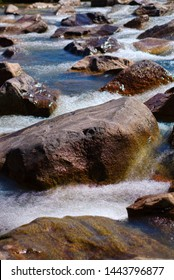 Roaring water flowing around rocks in wild river