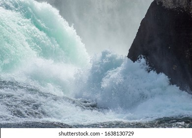 The roaring waters of the Rhine Falls between the rocks.