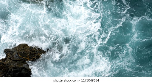 Roaring waves breaking on rocks cliff in Cinque Terre, Liguria, Italy. View from above.