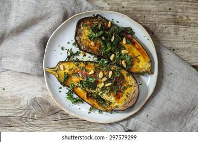 Roast aubergine with crispy kale and pine nuts