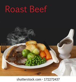 Roast Beef Concept - steaming hot roast beef with roast potatoes, brussels sprouts, carrots, peas and a jug of gravy, on a dark background with the words Roast Beef.