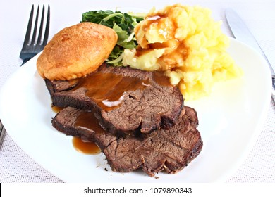 Roast beef with mashed potato and yorkshire pudding on a white plate, shallow focus