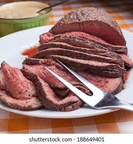 Roast beef on orange tartan tablecloth