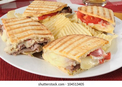 A roast beef panini sandwich with potato chips