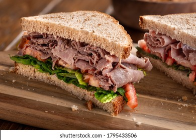 Roast beef sandwich with lettuce and tomato on whole wheat bread cut in half