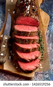Roast beef from tenderloin A large piece is cut into pieces. A large portion of meat served on a wooden board. Close up and vertical orientation.