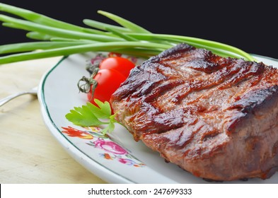 Roast beef  and vegetables on a plate with floral ornament on a wooden table