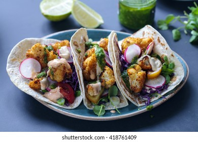 Roast cauliflower tacos with red cabbage, radish, tomatoes, spring onion, tahini sauce and chipotle sauce