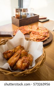 Roast chicken in a basket with pizza on wood table.