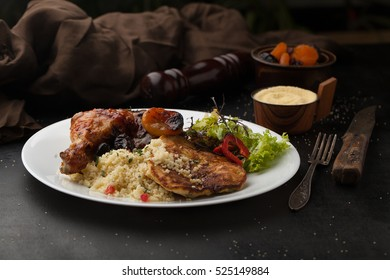 Roast chicken with couscous, spices and dried fruit on a dark background