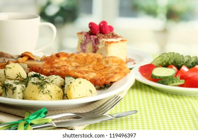 Roast chicken cutlet with boiled potatoes and cucumbers, cup of tea and dessert on green table cloth in cafe interior