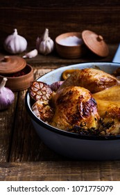 Roast chicken with garlic, thyme and lemon in cooking pan on rustic wooden background