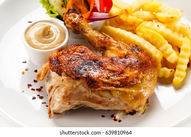 Roast chicken leg with french fries on white background