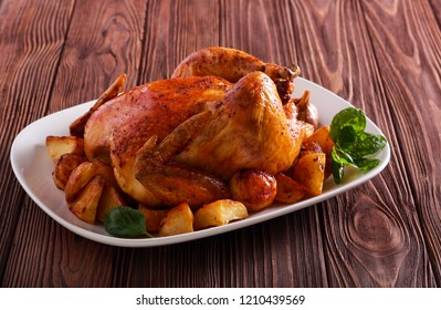 Roast chicken with potatoes on plate over wooden table