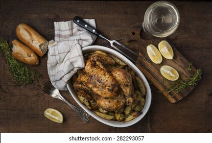 Roast chicken with potatoes on a wooden table in a rustic style