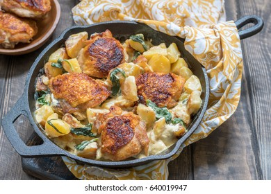 Roast chicken, potatoes and spinach with creamy sauce in a pan