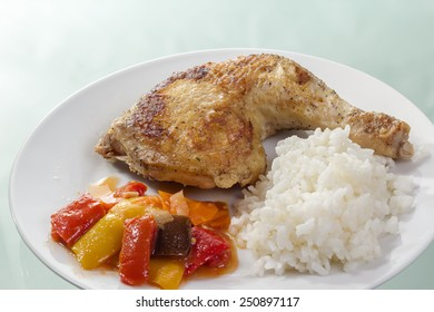 Roast chicken thigh with rice and vegetables on a white plate.