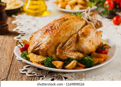 Roast chicken whole. Served on a plate with vegetables and baked potatoes. Front view.