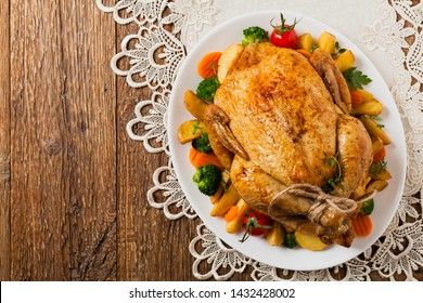 Roast chicken whole. Served on a plate with vegetables and baked potatoes. Flat lay. Top view.