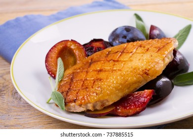 Roast duck brest with plums on white plate