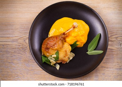 Roast duck leg with mashed pumpkin (butternut squash), sage and garlic on plate, closeup. Horizontal view from above, top shot