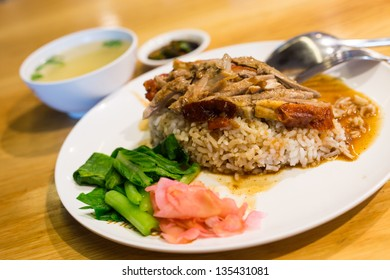 Roast Duck over Rice in plate  with sauce  and  soup