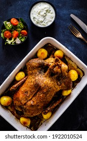 Roast duck in pot with vegetables on black wooden table