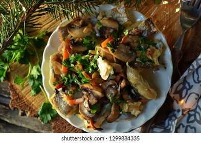 Roast fish with mushrooms on a white plate on a wooden disc