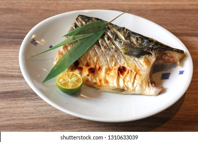 The roast mackerel with the bamboo leaf and kumquat decoration on a white dish. The traditional Japanese seafood.