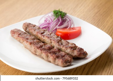 Roast meat on the white dish with vegetables : tomatoes, cucumbers, parsley and onion. on the wooden table